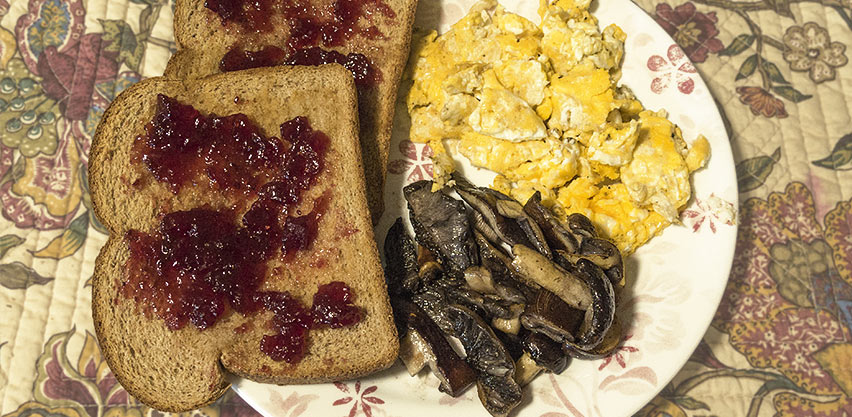 A delicious plate of sautéed wine caps with scrambled eggs, toast and jam